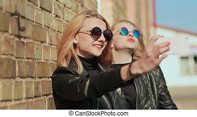 lunettes soleil, rue., mur, photo, mobile, selfie., petites amies, deux, téléphone, prendre, vestes, élégant, cuir, brique