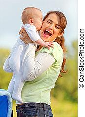mère, girl, tenant bébé, heureux, baisers, elle