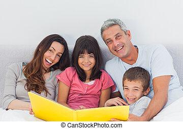 maison, leur, album, regarder, sourire, photographie, lit, ensemble, famille