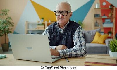 maison portrait, regarder, ordinateur portable, appareil photo, utilisation, homme, vieux, sourire, dactylographie, alors