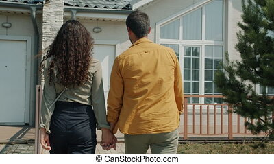 mari, marche, joyeux, épouse, nouveau, devant, conversation, maison, porte, sourire, dehors