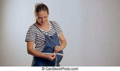 mesurer, debout, femme, elle, pregnant, contre, quoique, ventre, fond, blanc