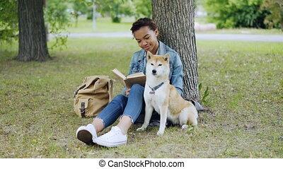 mignon, été, gai, propriétaire, girl, caresser, elle, day., livre, chiot, sac à dos, séance, parc, arbres, pelouse, lecture, visible., chien, course, vert, mélangé, herbe