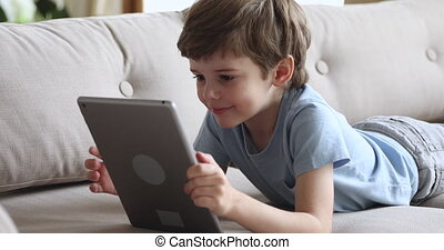 mignon, garçon, mensonge, sofa, seul, tablette, utilisation, heureux, préscolaire