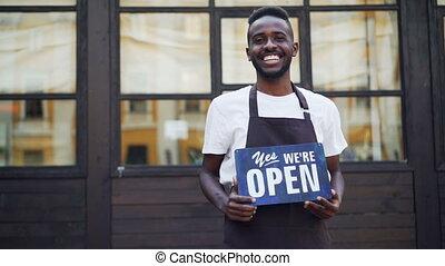 mouvement, portrait, signe, debout, ouvert, lent, dehors, appareil-photo., tenue, petit, américain, africaine, homme affaires, business, nous, propriétaire, concept., regarder, café, gai, jeunesse
