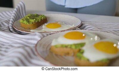 oeufs, femme, met, sain, vegan, plaque, toast., breakfast., frit, avocat