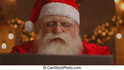 ordinateur portable, list., cheminée, fonctionnement, sien, enfants, utilisation, noël, claus, chaise, séance, souhait, réception, sourire, arbre, communication, nouveau courrier, gai, santa, ou, quoique, technologie, vrai