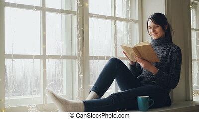 porter, noël, window-sill, séance femme, chandail, jeune, sourire, livre, jeans., rêveur, branché, lecture fille, illumination., décoré