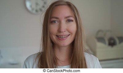 portrait, femme, bureau, fin, bretelles, appareil-photo., clinique, jeune, dent, fond, braces., sourire, regarder, heureux, sourires, haut, dentaire