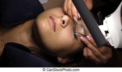 procedure., haut, mèches, oeil, eyelashes., cil, extension., sélectionné, cosmétique, artificiel, foyer., mensonges, lampe, femme, long, sous, fin, gluing, cils, tweezers.