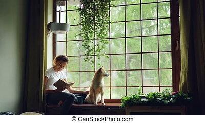 purebred, animaux, étudiant, elle, séance, apartment., concept., moderne, chien, fenêtre, livre, séduisant, rebord, africaine, intérieur, américain, lecture fille, caresser, passe-temps