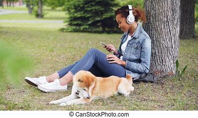 quoique, smartphone, manger, elle, séance, écouteurs, parc, grass., chien, femme américaine, musique, séduisant, écoute, africaine, utilisation, herbe, mensonge, tout