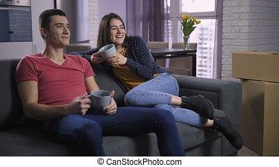 regardant télé, couple, après, boîtes, déballage