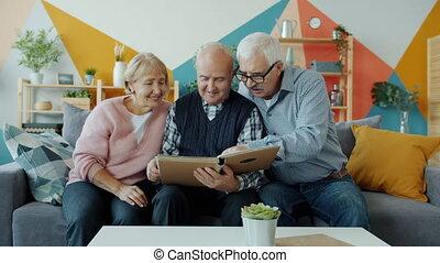 regarder, groupe, photos, divan, séance gens, maison, conversation, personnes agées, album