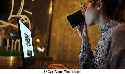 regarder, ordinateur portable, café, utilisation, jeune, travailleur indépendant, café, boire, séance, moniteur, femme, nuit