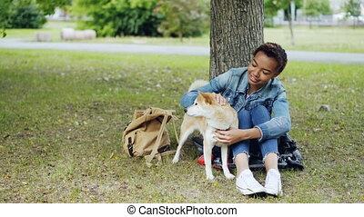 reposer, gentillesse, femme, animaux, adoration., gens, chouchou, concept., parc, jeune, conversation, américain, pelouse verte, africaine, chiot, adorable, caresser