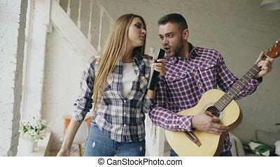 rigolote, femme, heureux, danse, chant, couple, guitar., aimer, leur, contrôleur, avoir, tv, amusement, maison, vacances, pendant, jouer, homme