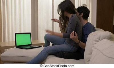 rigolote, projection, faire idiot, couple, autour de, film regardant, ordinateur portable, jeune, étreindre, quoique, sofa vert, maison, blanc écran, affection, baisers