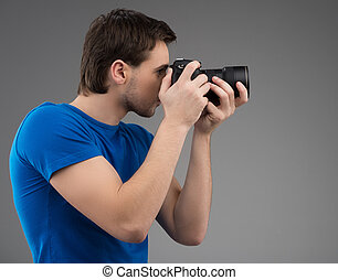 sien, appareil-photo., gris, jeune, isolé, confiant, quoique, appareil photo, tenant mains, concentrer, vue, côté, homme