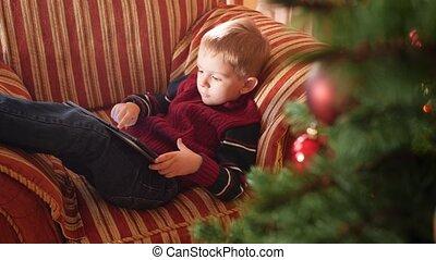sofa, salle, métrage, matin, noël, computer., délassant, vivant, amusement, jouer, enfantqui commence à marcher, enfant garçon, après, 4k, avoir, peu, tablette, fetes, celebrations., hiver, numérique