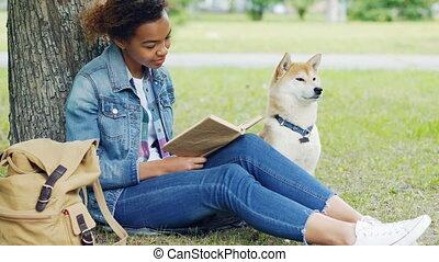 style de vie, nearby., herbe, animaux, étudiant, elle, nature, concept., moderne, parc, chien, américain, livre, obéissant, joli, africaine, portrait, séance, lecture