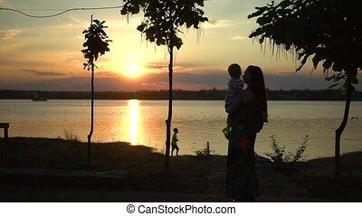 tenant mains, étreindre, rayons, coucher soleil, mère, son, silhouette, beau, mer, affectueux, exprimer, mignon, amour, care., enfantqui commence à marcher, apprécier