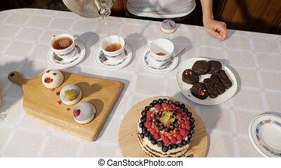 thé, femme, verser, bonbons, birthday., mains, maison, tasses, table, célébrer