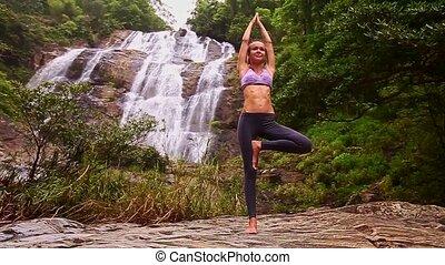 tient, yoga, jambe, pose, contre, une, cascade, chute eau, girl