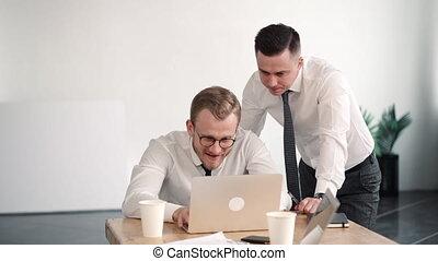 travail, discuter, business, ordinateur portable, jeune, regard, hommes affaires, bureau, deux, réussi, table.