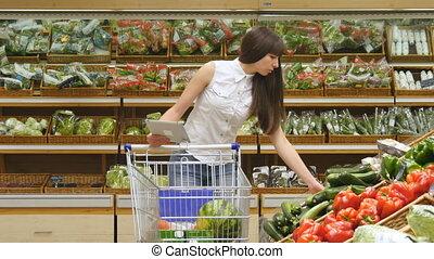 trolley., les, achats femme, frais, tablette, légumes, pousser, jeune, charrette, pc, list., mettre, supermarché, choisir, utilisation, long, allées, girl, chèque, épicerie