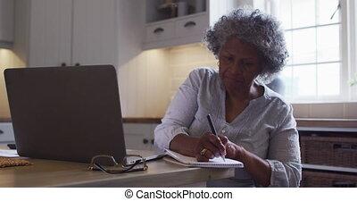 utilisation, africaine, ordinateur portable, femme aînée, prise notes, américain, maison