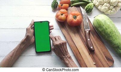 utilisation, main, intelligent, téléphone, femmes, légumes, frais, table, personne agee
