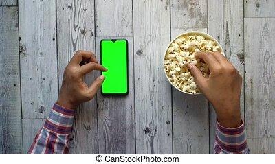 utilisation, main, téléphone, homme, intelligent, manger, pop-corn