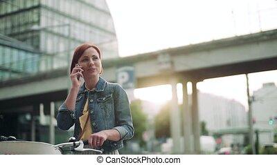 vélo, femme, dehors, city., banlieusard, debout, smartphone, jeune