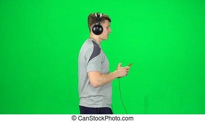 va, grand, écouteurs, texting, homme, écran, smartphone, vert, vue côté, studio.