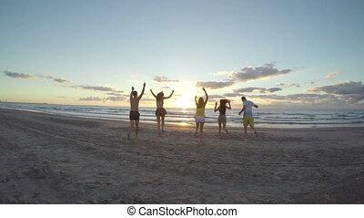 vers, hommes, jeune, courant, mer, plage, sablonneux, femmes