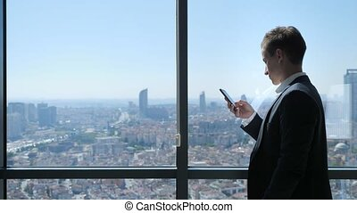 ville, bureau, panoramique, jeune, téléphone, fenêtre, brouter, homme affaires, vue.