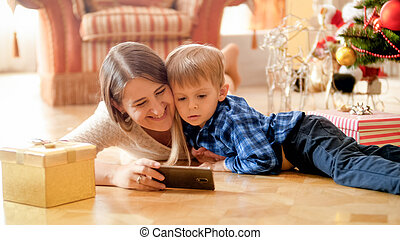 vivant, smartphone, salle, garçon, regarder, arbre, noël, vidéo, sous, portrait, sourire, enfantqui commence à marcher, mère, mensonge, heureux