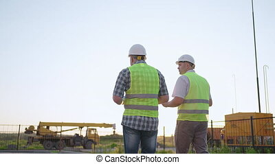 waist-up, constructeurs, sécurité, porter, habillement, papier, projet, deux, construction, homme, plan, site, talkie-walkie, collègue, debout, mâle, tenue, sien, deux âges, utilisation